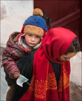 A baby boy with his donation is carried on his mother's back up to the monastery.