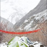 Tents in the snow under a string of Buddhist prayer flags.
