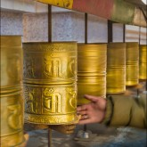 The hand of a Ladakh resident spins the long row of prayer wheels as he passes by.