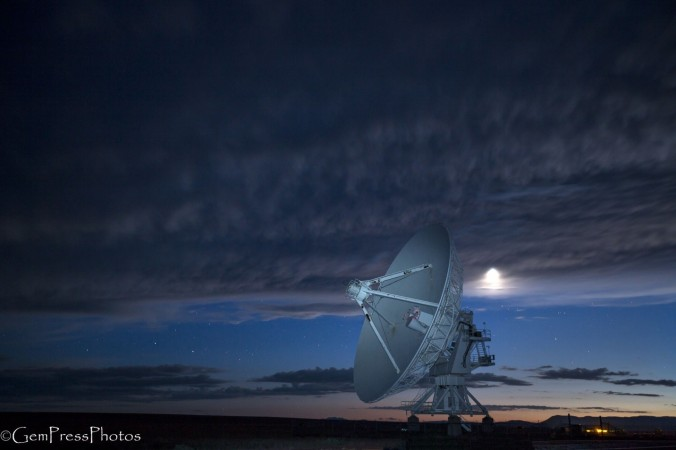 VLA Radio telescope, one of 39 in the array with the setting moon and light by a car traveling north from Reserve NM